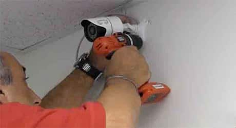 A man using a power drill to attach a security camera to a wall.
