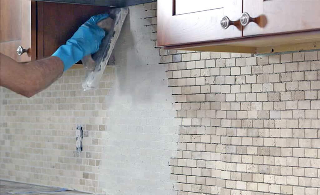 A man applying grout to a tile backsplash.