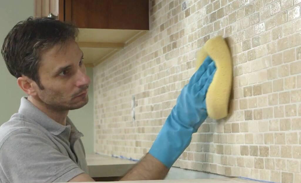 A man wiping down a tile backsplash.