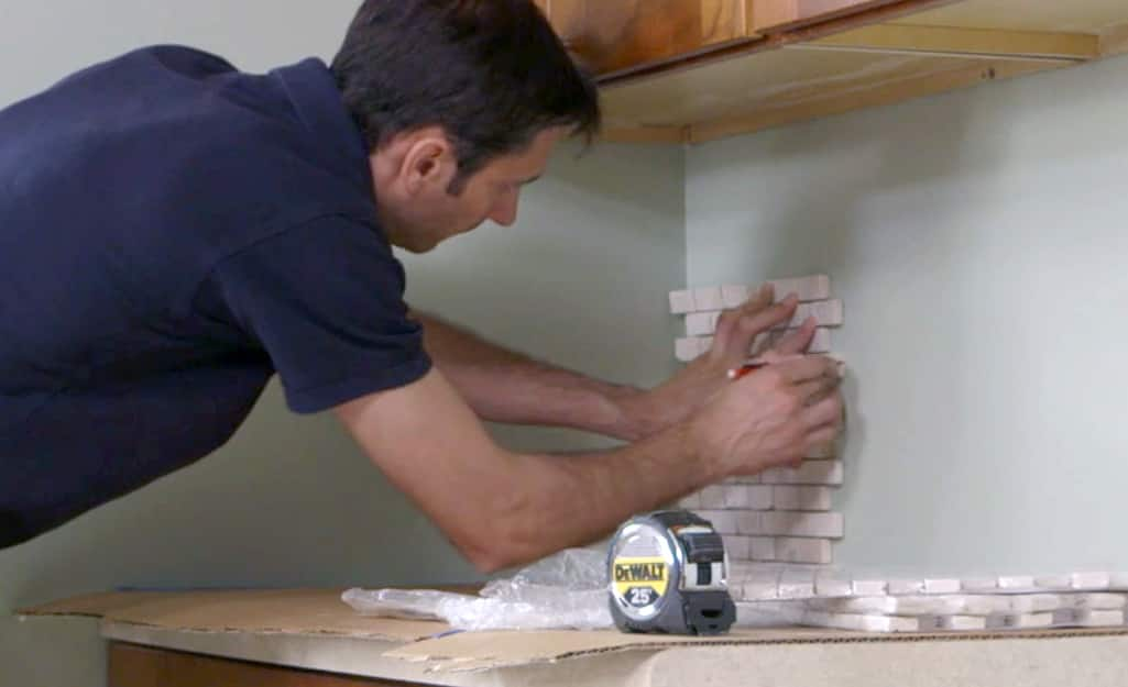 A man laying tile onto a wall.