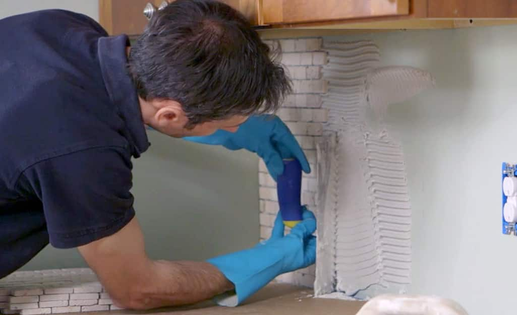 A man laying tile onto a kitchen wall.