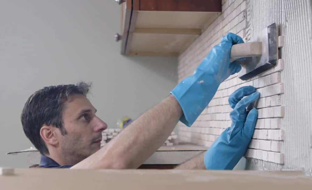 A man using a trowel to press tile into a wall.