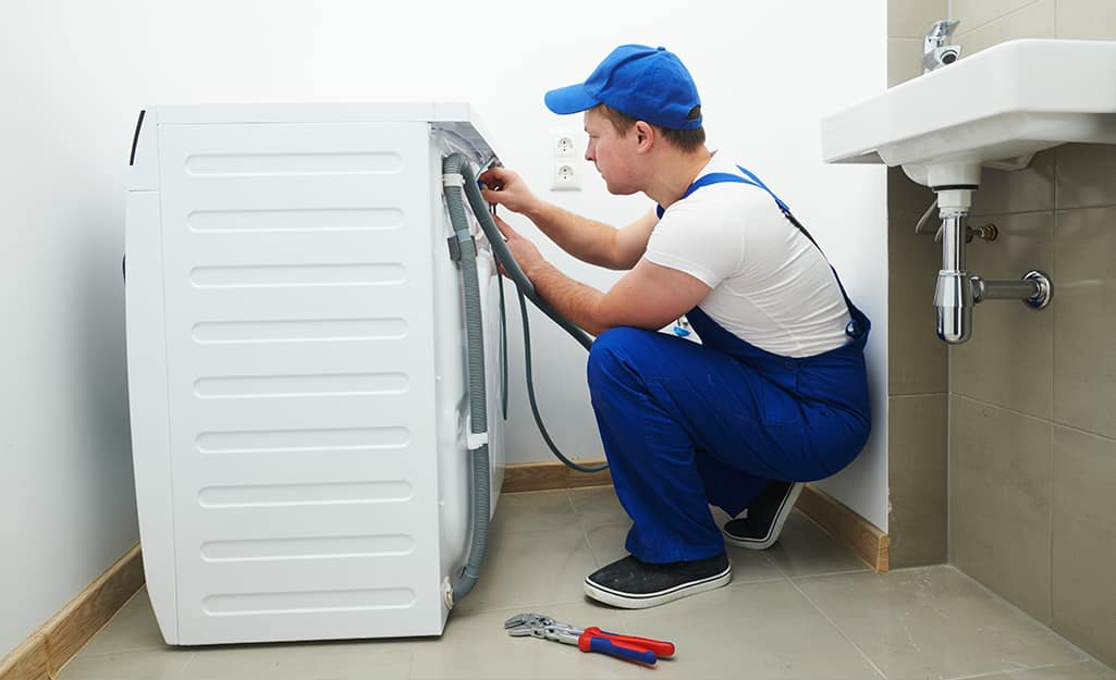 A person working on the back of a washing machine near a sink.