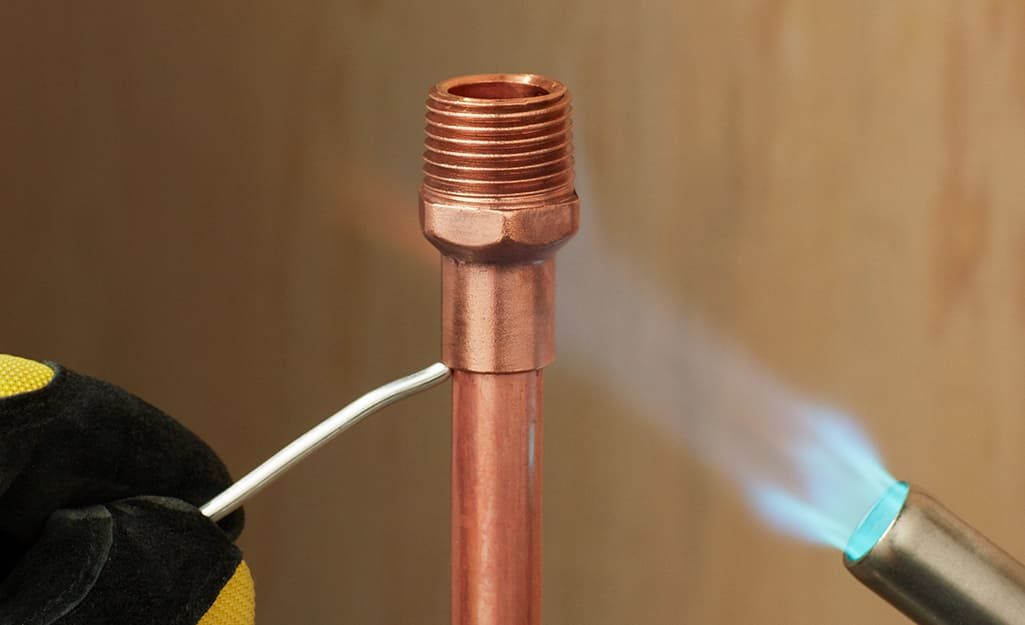A person soldering a connection on a copper pipe.