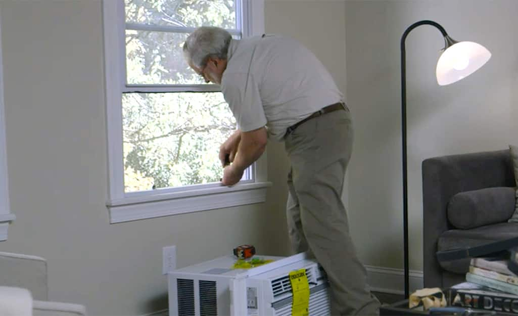 A person securing a support bracket to install a window air conditioner.