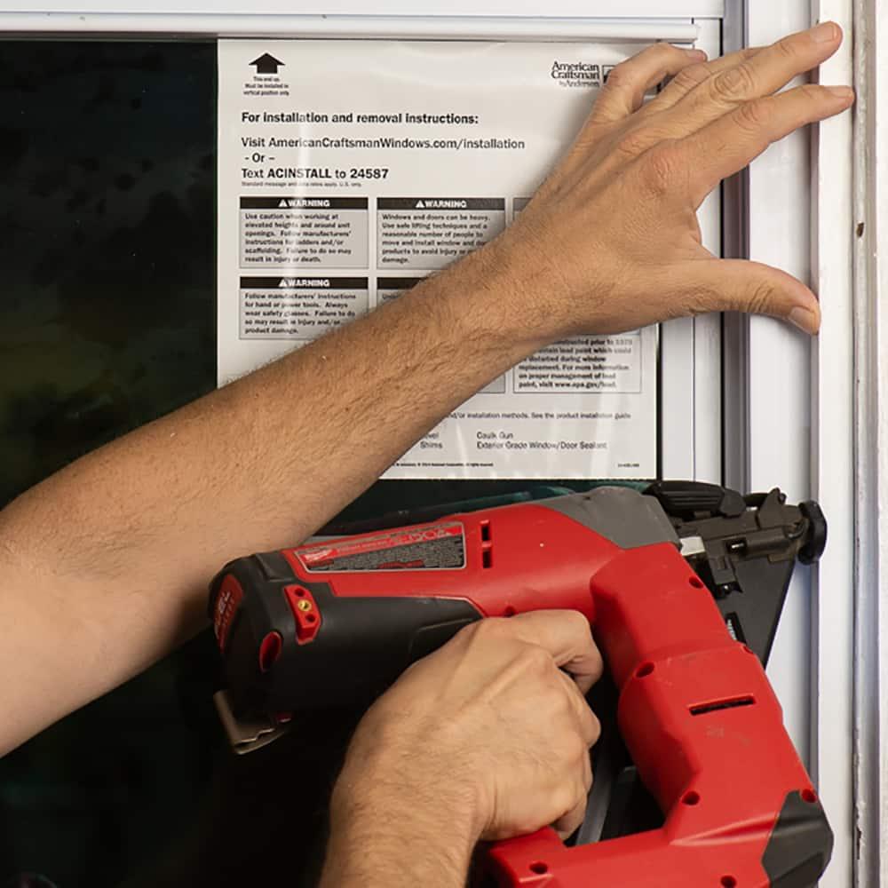 Someone fastening trim on a remodel window.