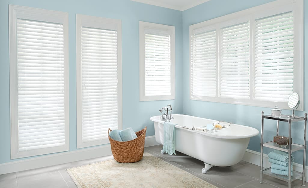 Faux wood blinds on windows in a bathroom.