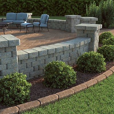 A bed of shrubs with brick edging around the perimeter of a patio.