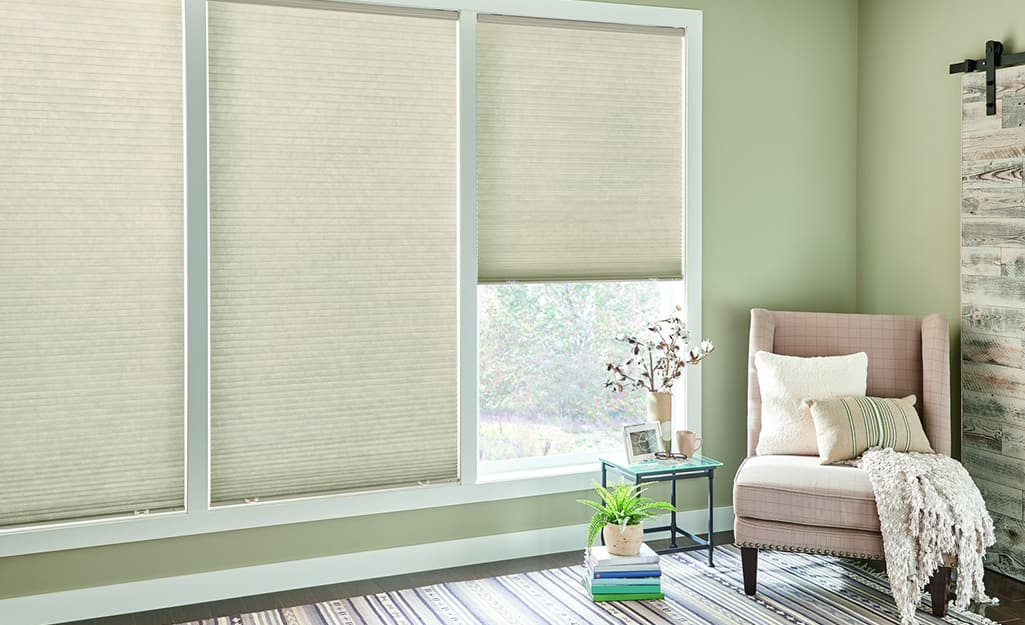 A room with three windows covered by cellular shades mounted inside the window frames.