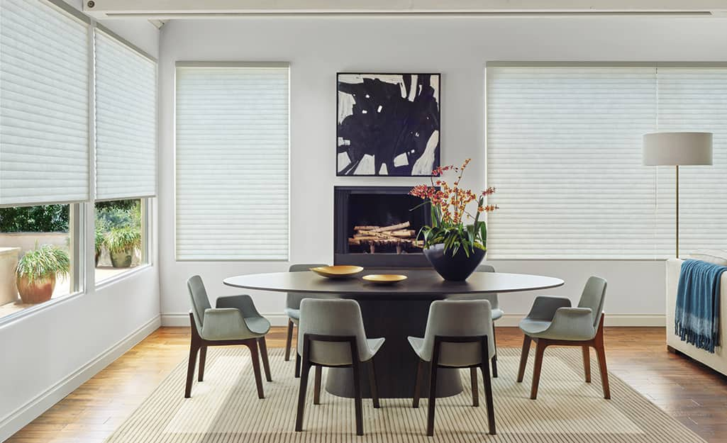 A dining room with windows covered by cellular shades mounted outside the window casings.