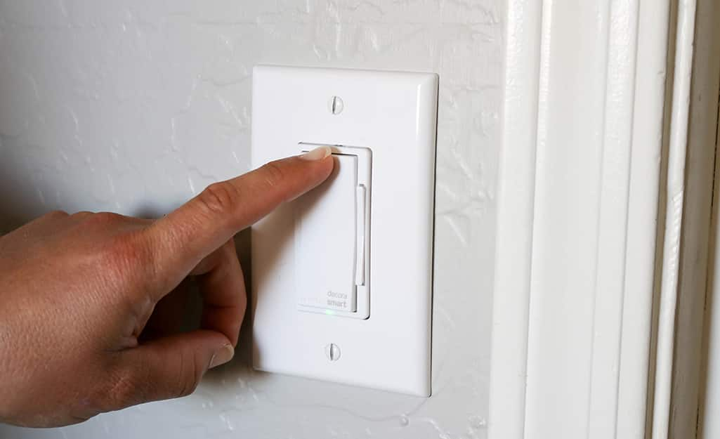 A person touches the dimmer switch to test the power.