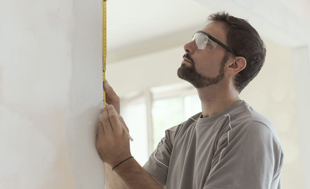 person using a set square to measure a door jamb