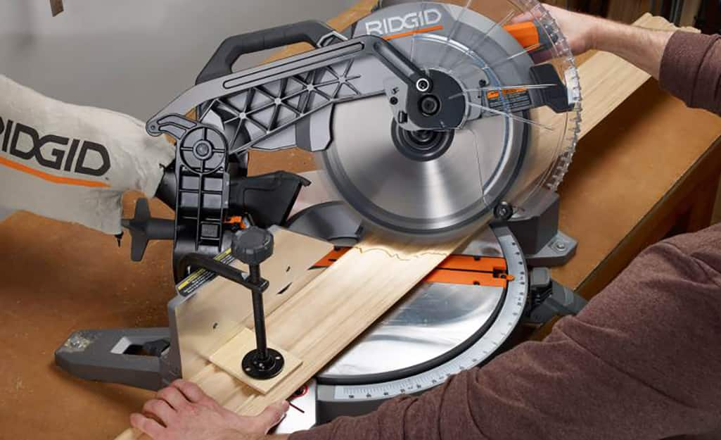 person cutting wood for trim using a miter saw