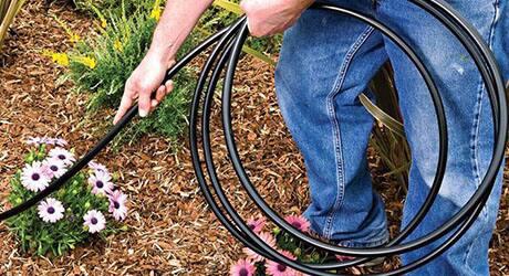 Someone placing drip irrigation hosing through a flower garden.