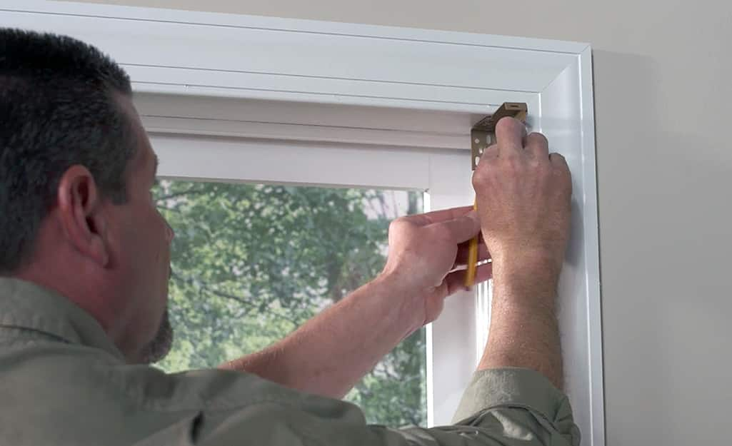 A man installs mounting brackets to hang blinds.