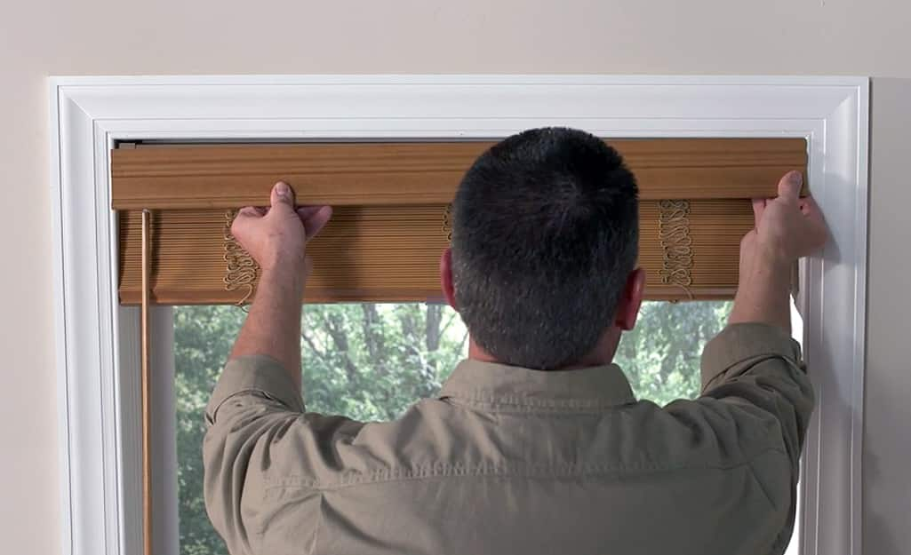 A man hangs the valance clip for his faux wood blinds.