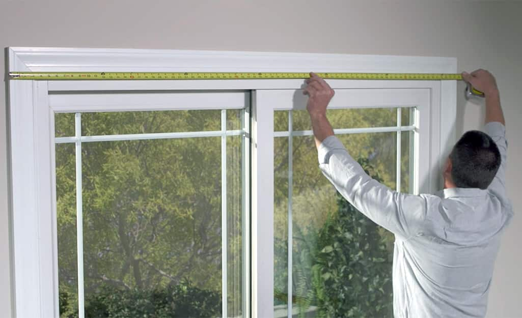 A man measures the width of a window before installing blinds.
