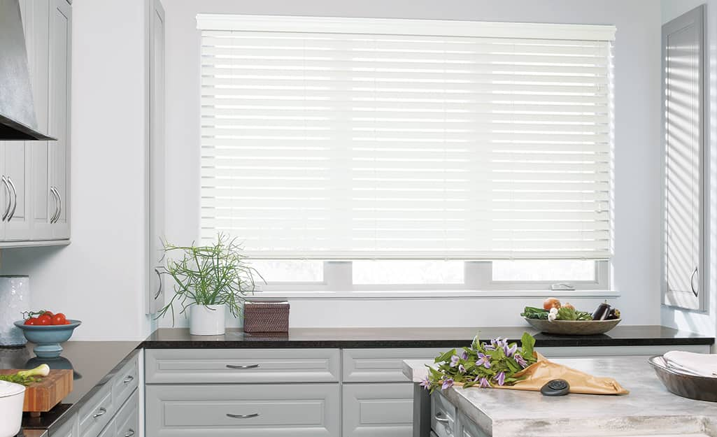 New faux wood blinds hang inside of a kitchen.