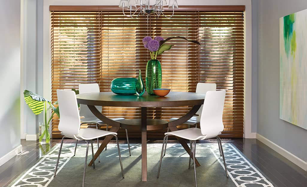 Wooden horizontal blinds cover French doors and windows in a dining room.