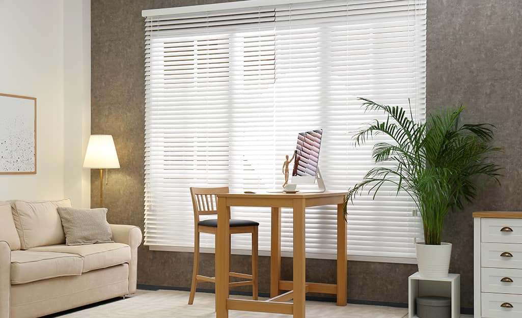 Outside mount horizontal blinds cover the windows in a small living room.