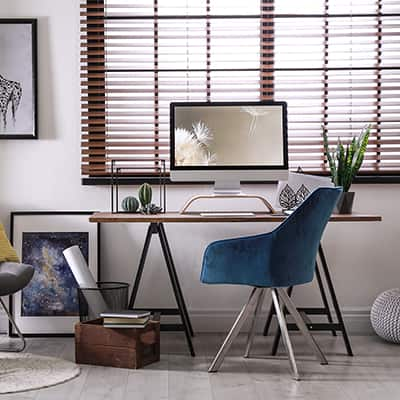 Horizontal blinds hang in a home office.