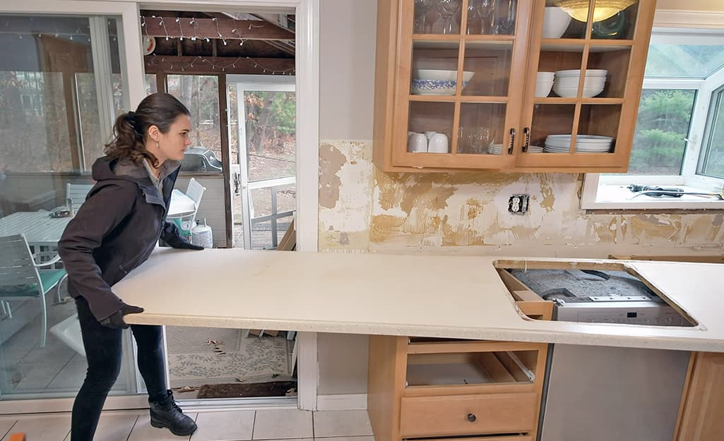 A woman helps to remove an old counter top.