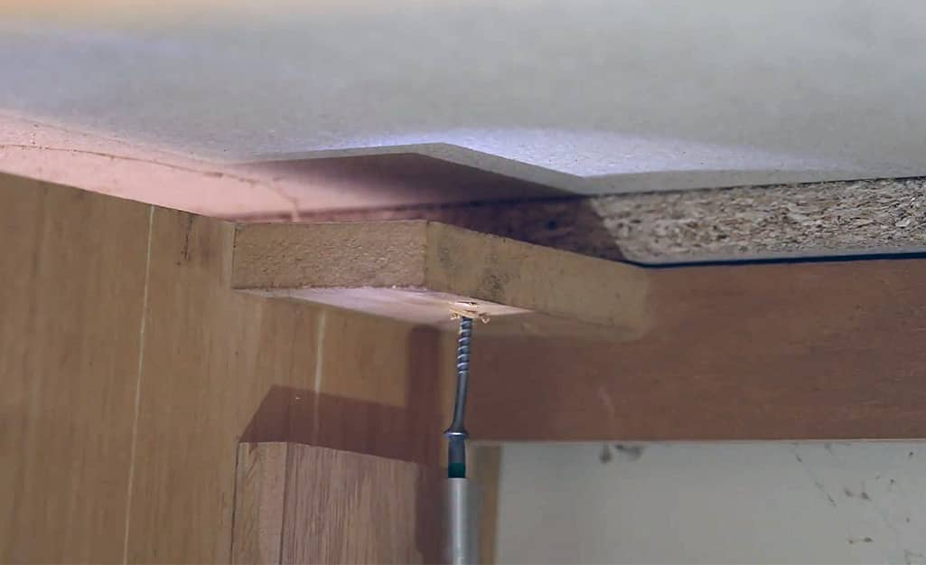 A countertop is secured to a cabinet with a screw.