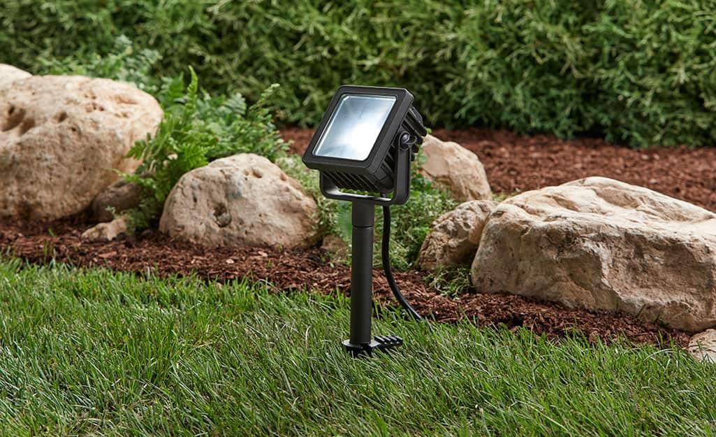 A line voltage spotlight installed in a yard near a garden bed.