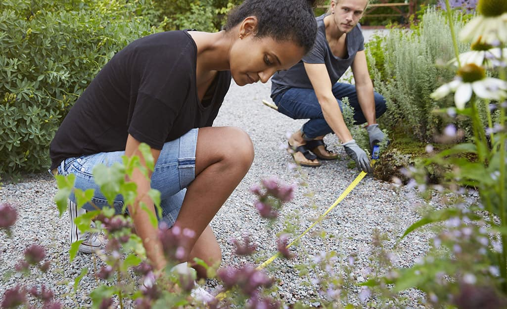 Two people using a steel measuring tape to measure a gravel garden path.