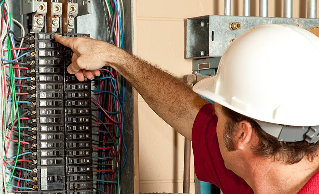An electrician switching a circuit breaker in an electrical panel.