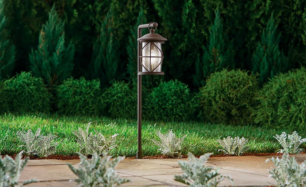 A lantern style low voltage landscape light installed next to a walkway.