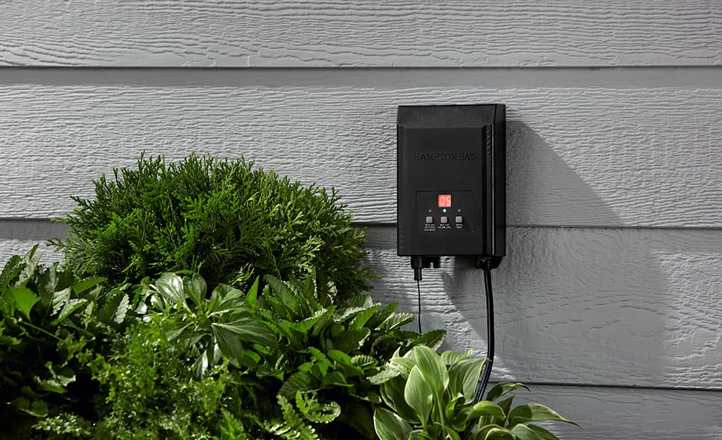 A low voltage landscape lighting transformer mounted to the side of a house.