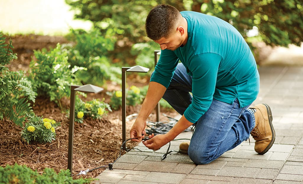 A man connecting the cables of a row of low voltage landscape lights.