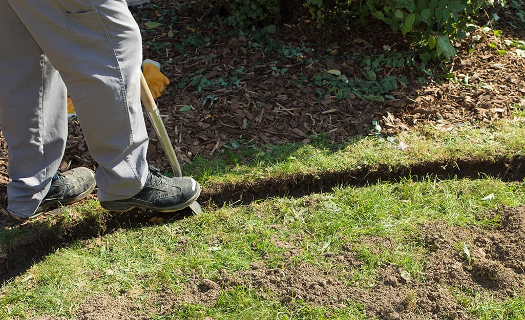 A person digging a narrow trench along a garden bed for the landscape lighting cable.