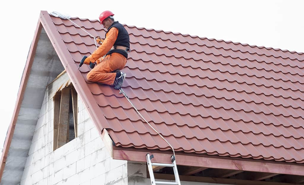 A man wears safety gear to install roofing.