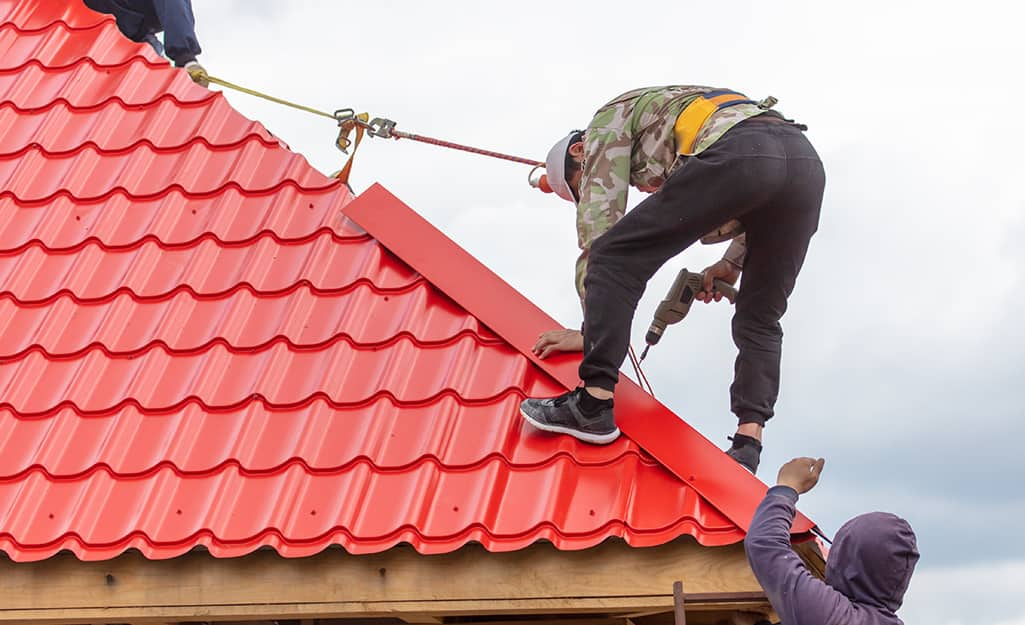 Two workers use safety gear to install a roof's ridge cap.