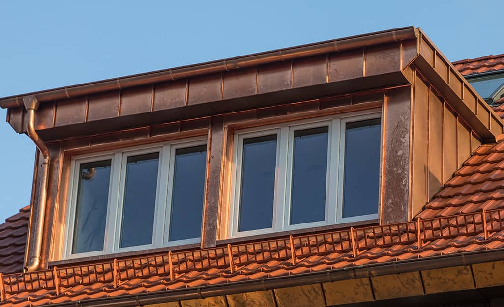 A home features a copper roof and attic windows.