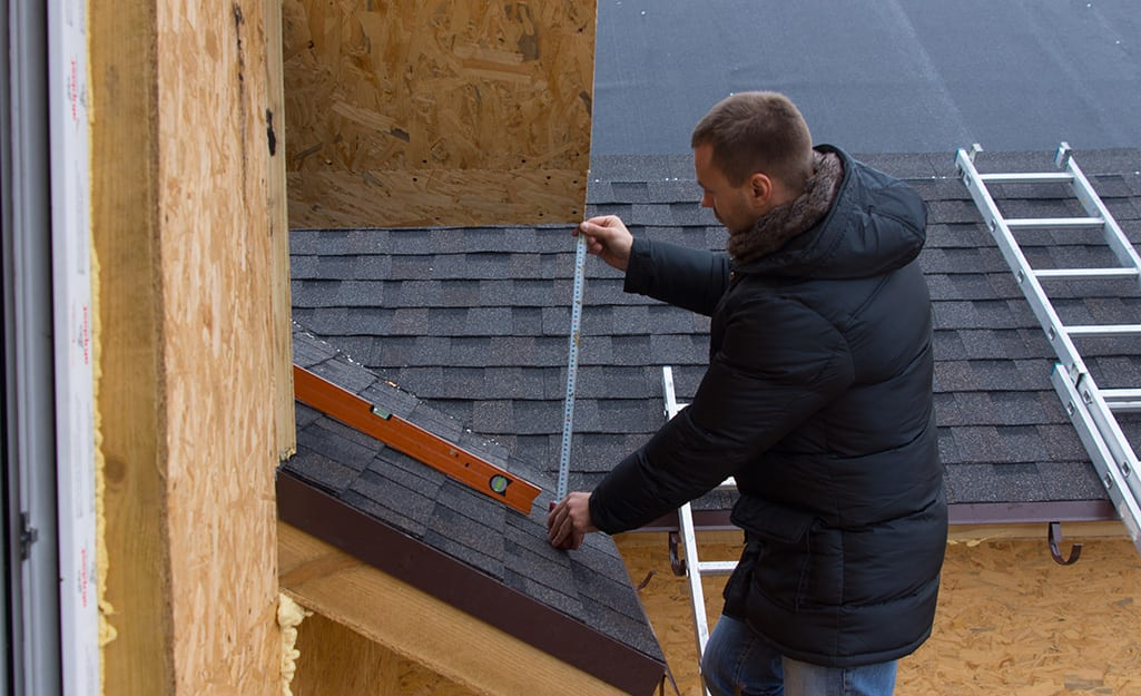 A man wears a winter coat while measuring a roof.