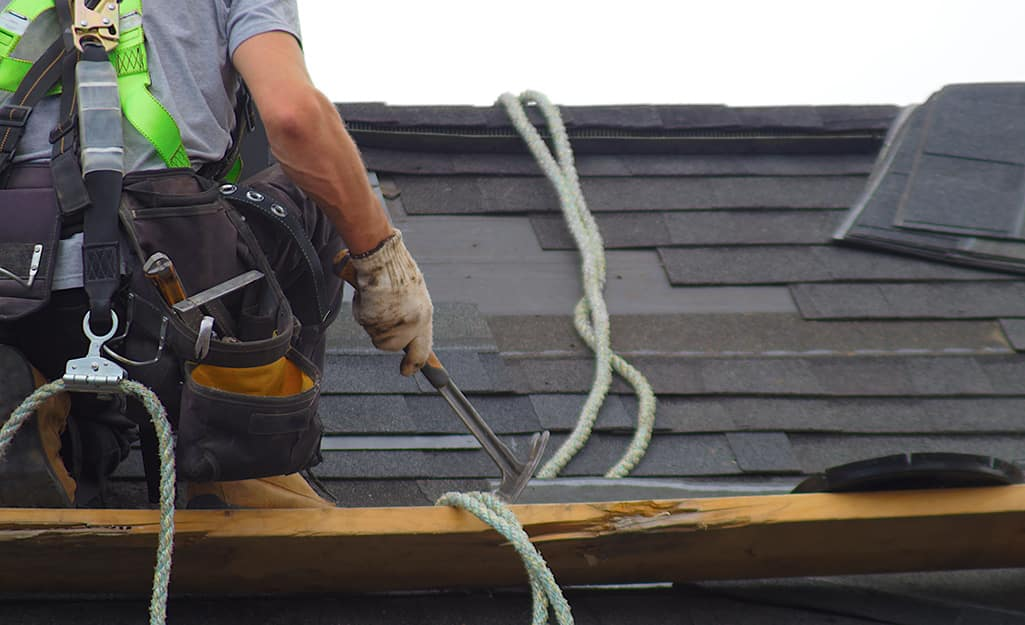 A person uses a hammer to remove old roofing.