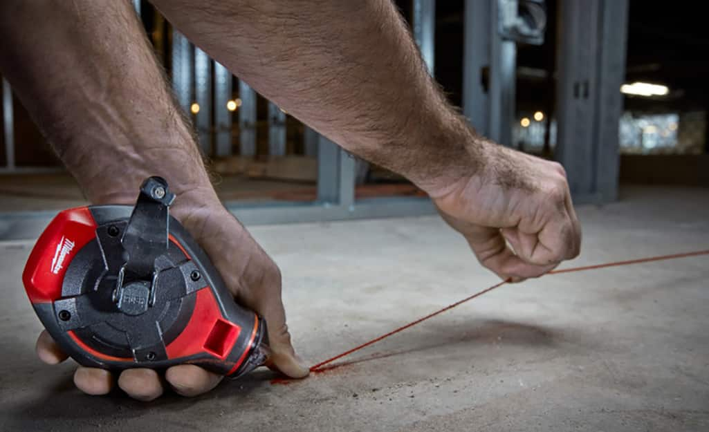 A man snaps a chalk line before installing flooring.