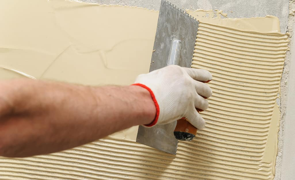 A person adds adhesive before installing flooring.