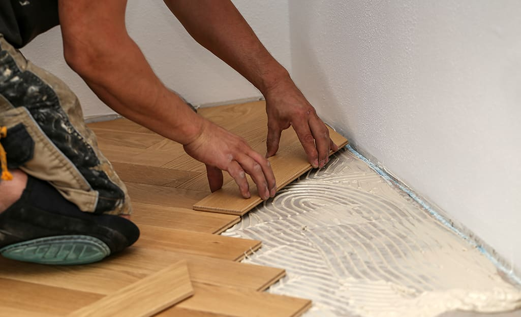 A person lays tile down on adhesive.