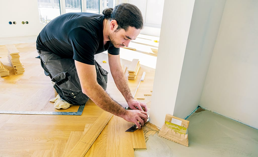 A man cuts the tile to fit the wall.