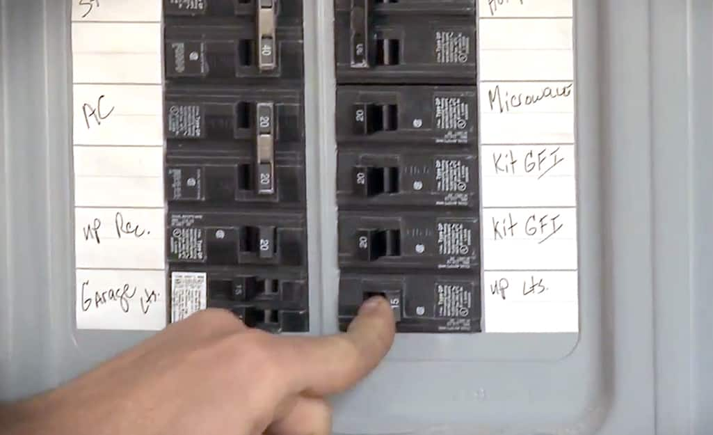 A person switching a fuse at an electrical box.