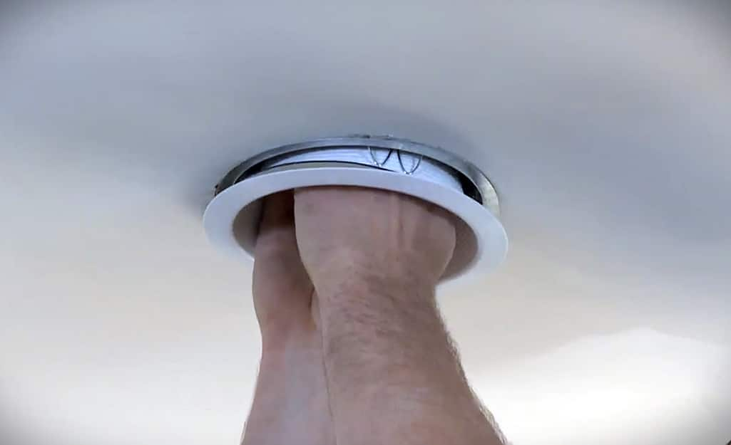 A person connecting recessed lighting trim to the recessed light housing.
