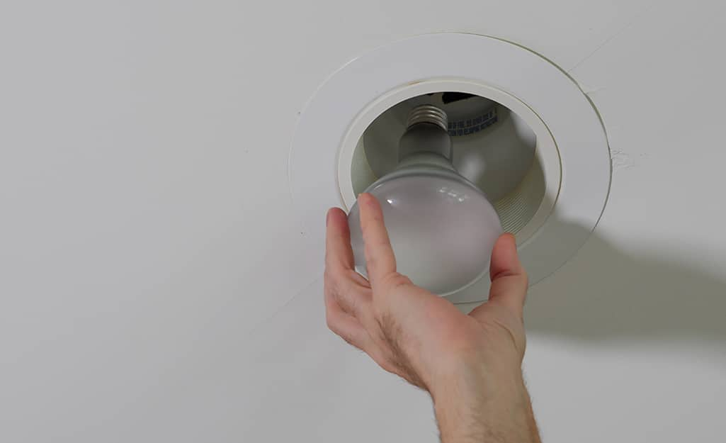A person installing a light bulb into a recessed light.