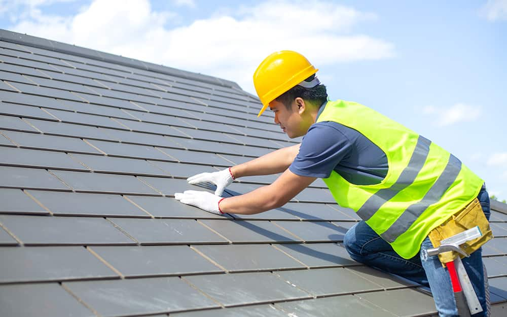Man preps the roof for shingles.