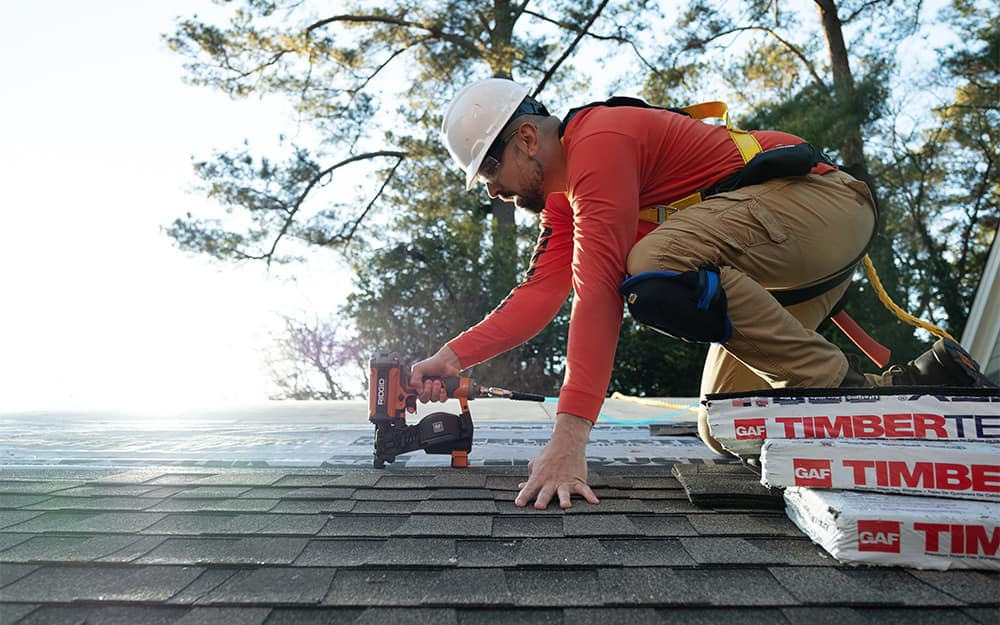 Man finishes laying roof shingles.