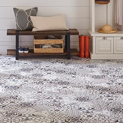 A blue and white tile floor installed in an entryway.