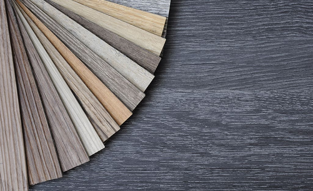 Different swatches of luxury vinyl plank flooring are fanned out over a vinyl floor.